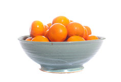 Bowl filled with mandarin oranges. Green pottery bowl filled with mandarin oranges stock images
