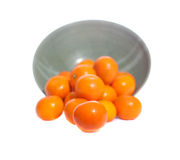 Bowl filled with mandarin oranges. Dozens of mandarin oranges spilling from a pottery bowl royalty free stock photo