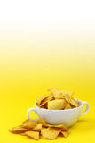 Bowl filled with nacho chips. On a yellow to white background Stock Photography