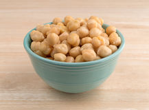Bowl filled with organic garbanzo beans on table. A bowl filled with organic garbanzo beans on a wood table stock images