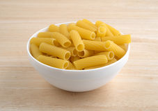 Bowl filled with rigatoni pasta on wood table Stock Image