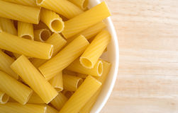 Bowl filled with rigatoni pasta on wood table Royalty Free Stock Photos
