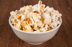 Bowl filled with salt popcorn on a wooden table. Close up royalty free stock photos