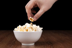 Bowl filled with salt popcorn on a wooden table and human hand. On a black background stock image