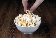 Bowl filled with salt popcorn on a wooden table and human hand. Close up stock photos