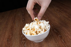Bowl filled with salt popcorn on a wooden table and human hand. Close up stock photo