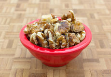 Bowl filled with shelled walnuts on chopping block Stock Photography