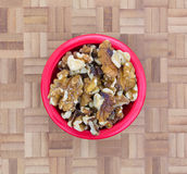 Bowl filled with shelled walnuts on chopping block Stock Image