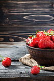 Bowl filled with succulent juicy fresh ripe red strawberries on an old wooden table Stock Photo