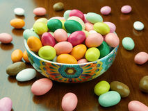 Bowl filled up with colored sugared almonds. On the table stock photography