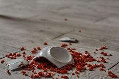 Bowl on the floor. Shattered bowl of porcelain on the floor containing pepper Royalty Free Stock Photography