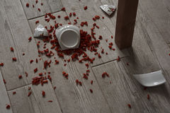 Bowl on the floor. Shattered bowl of porcelain on the floor containing pepper Stock Photo