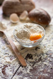 Bowl of flour with egg and bread Royalty Free Stock Images