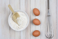 Bowl of Flour Eggs and Whisk Royalty Free Stock Photography