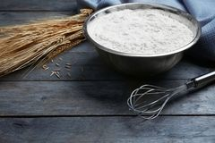 Bowl with flour, wheat and corolla. On wooden table Royalty Free Stock Photography