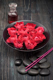 Bowl with flowers roses, black stones and rose oil Royalty Free Stock Photography