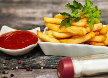 Bowl of french fries with tomato sauce. And bottle of salt on the table Royalty Free Stock Photo