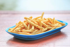 Bowl of french fries on wooden table Stock Image