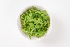 Bowl of fresh arugula. Leaves on white background Stock Photography