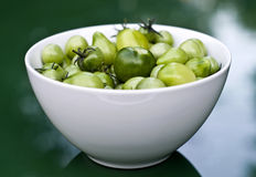 Bowl of fresh baby green tomatoes. A bowl of baby green tomatoes in a white bowl, on a green background. Shallow depth of field Stock Photos