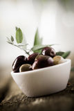 Bowl of fresh black olives. Tilted view of a bowl of fresh black olives with shallow dof and copyspace Royalty Free Stock Photography