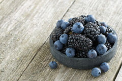 bowl of fresh blackberries and blueberries on wooden background Royalty Free Stock Photo