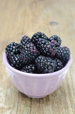 Bowl of fresh blackberries on a wooden background Stock Photos