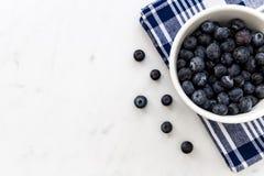 Bowl of fresh blueberries on white marble background. Bowl of fresh blueberries fruit on white marble background Stock Photo