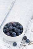 Bowl of fresh blueberries on white wooden background, vertical. Top view Stock Photos