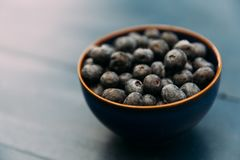 Bowl of blueberries on wood table Stock Images