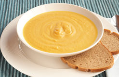 Bowl of fresh butternut soup. Bowl of fresh hot butternut soup served with rye berliner bread Stock Images