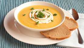 Bowl of fresh butternut soup. Bowl of fresh hot butternut soup with cream and parsley, served with rye berliner bread Royalty Free Stock Photography