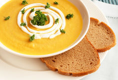 Bowl of fresh butternut soup. Bowl of fresh hot butternut soup with cream and parsley, served with rye berliner bread Stock Image