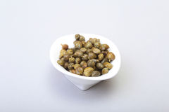 Bowl with fresh capers  on white background. Bowl with fresh capers  on white background Royalty Free Stock Image