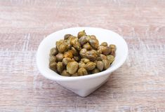 Bowl with fresh capers on wooden table.  Royalty Free Stock Photography