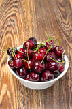 Bowl of fresh cherries on a wooden background, top view Stock Image