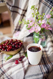 Bowl with fresh cherry berries and cup of tea and flowers, summer snacks Royalty Free Stock Image
