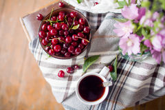 Bowl with fresh cherry berries and cup of tea. Top view Royalty Free Stock Photography