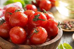 Bowl with fresh cherry tomatoes, spinach and olive oil, close-up Stock Image