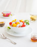Bowl of fresh exotic fruit salad on white summer background Healthy breakfast Royalty Free Stock Image
