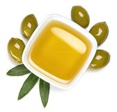 Bowl of olive oil and green olives with leaves Royalty Free Stock Images