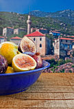 Bowl of fresh figs on rustic wooden table against village backgr Stock Photo