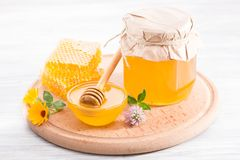 Bowl with fresh flower honey and honeycomb. On a wooden board Stock Photography