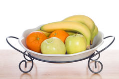 Bowl of Fresh Fruit. Assorted fresh fruit including bananas, oranges and apples, sitting in a bowl and shot on a wooden table Royalty Free Stock Image