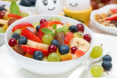 Bowl of fresh fruit salad and painted eggs for breakfast Royalty Free Stock Images
