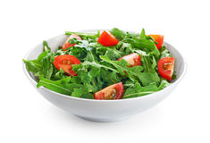 Bowl with fresh green salad arugula and tomatoes  on whi Stock Photo