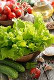 Bowl with fresh green salad, vegetables, spices and olive oil Stock Image