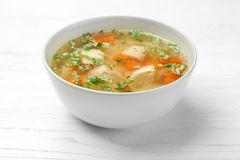 Bowl with fresh homemade chicken soup on table. Bowl with fresh homemade chicken soup on wooden table royalty free stock images