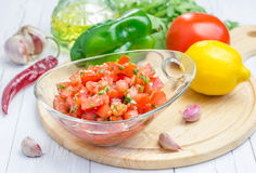 Bowl of fresh homemade salsa dip and ingredients. Closeup Royalty Free Stock Image