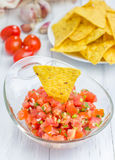 Bowl of fresh homemade salsa dip with nachos. Closeup Royalty Free Stock Images